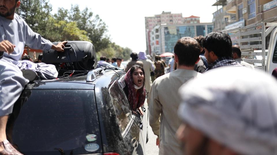 La tête d'une femme qui crie apparaît du côté passager d'une voiture. Des hommes marchent aux côtés de la voiture.