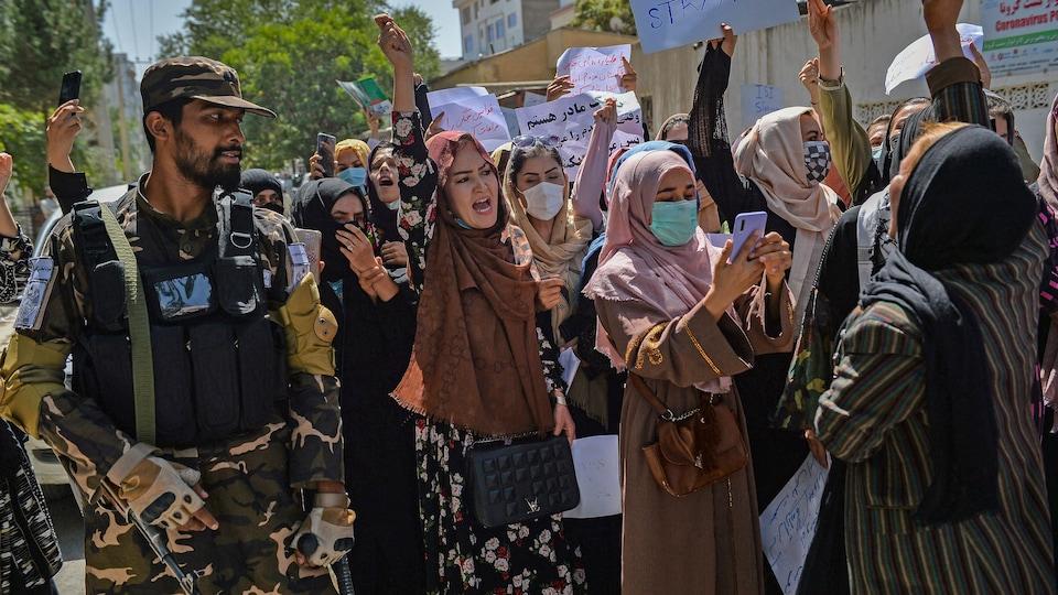 Des femmes manifestent tout près d'un combattant taliban.