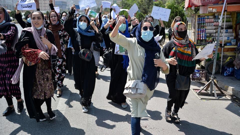 Des femmes marchent dans une rue. Plusieurs brandissent un poing en l'air. Leur visage n'est pas voilé, mais beaucoup d'entre elles portent un masque.