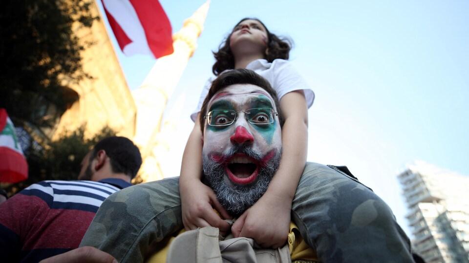 Un homme avec le visage maquillé de rouge et de vert et qui porte sur ses épaules une fillette.