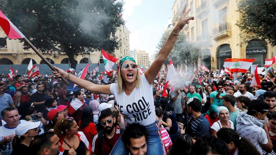 Une femme tient le drapeau du Liban et est assise sur les épaules d'un homme. Tout autour d'elle, une foule de manifestants.