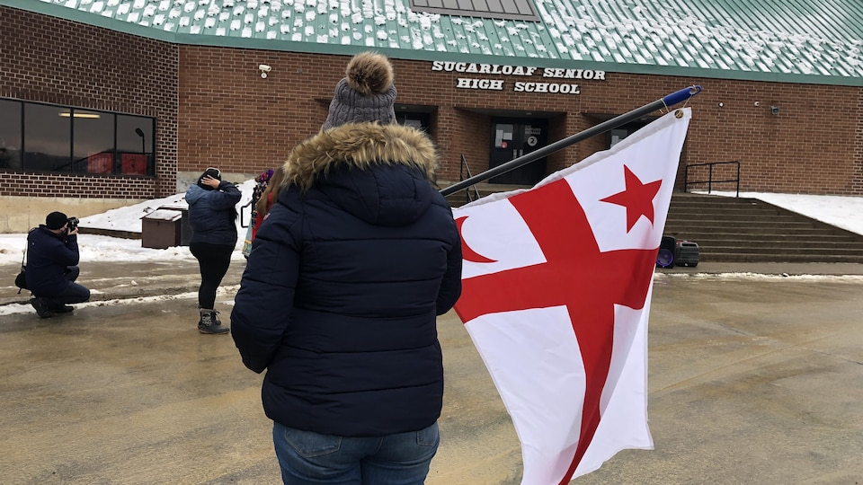 Une personne de dos avec un drapeau micmac devant l'école Sugarloaf.