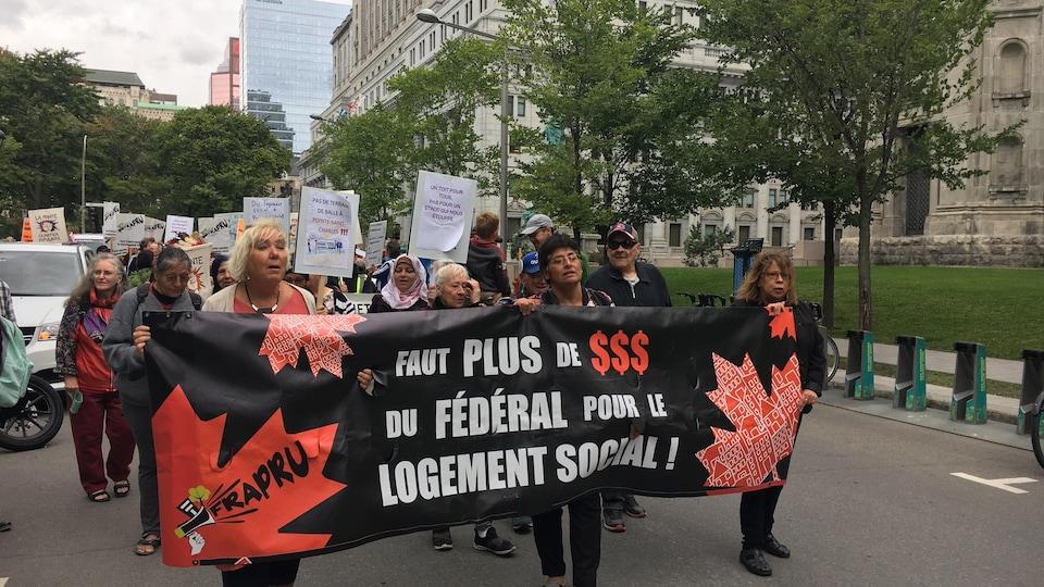 Des manifestants tiennent une banderole sur laquelle on peut lire «Faut plus de dollars du fédéral pour le logement social».