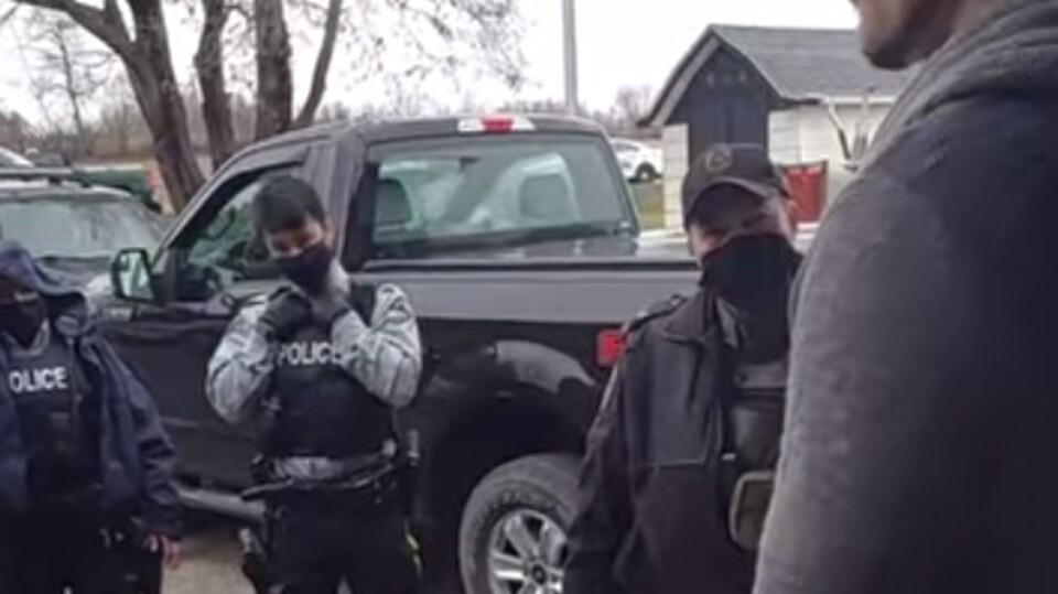 Des policiers à l'extérieur parle avec un homme de dos.