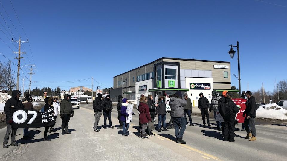 Une vingtaine de manifestants avec des pancartes à la main dans la rue devant un commerce en hiver.