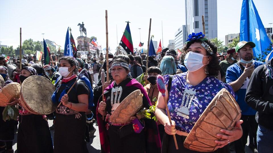 Des femmes autochtones avec des tambours et des masques dans une manifestation.