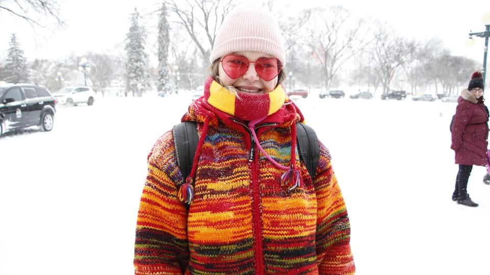 Une jeune femme souriante dans la neige.