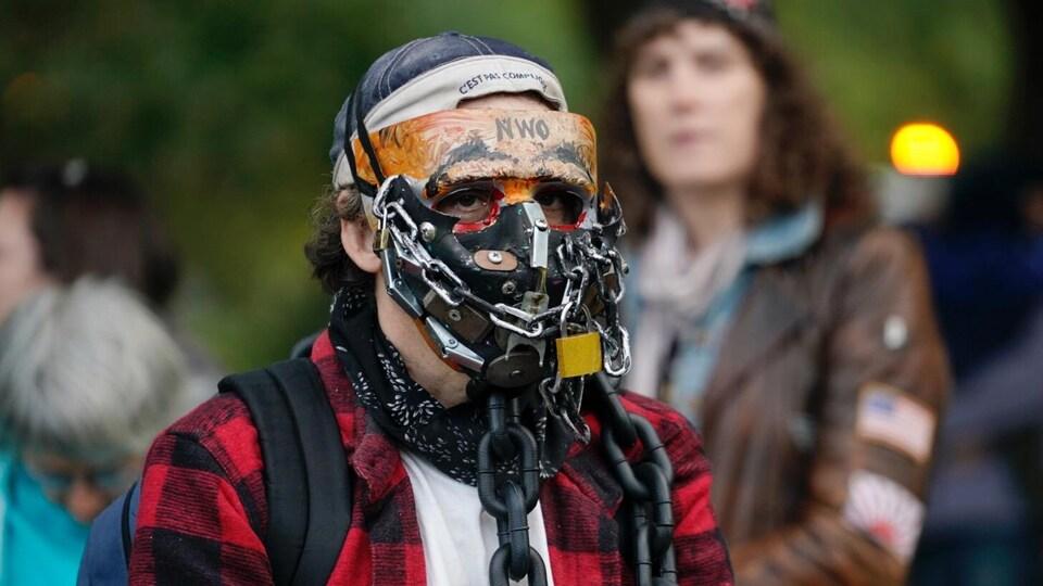 Un homme porte un masque fait de chaînes métalliques.