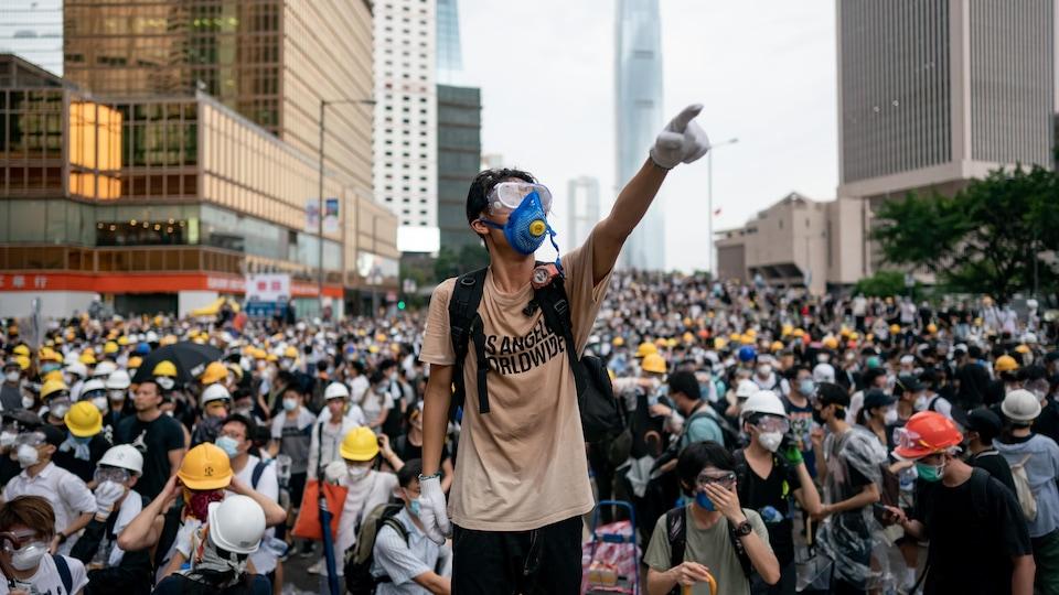 Un jeune portant un masque se tient debout, bras levé, devant une foule de manifestants.