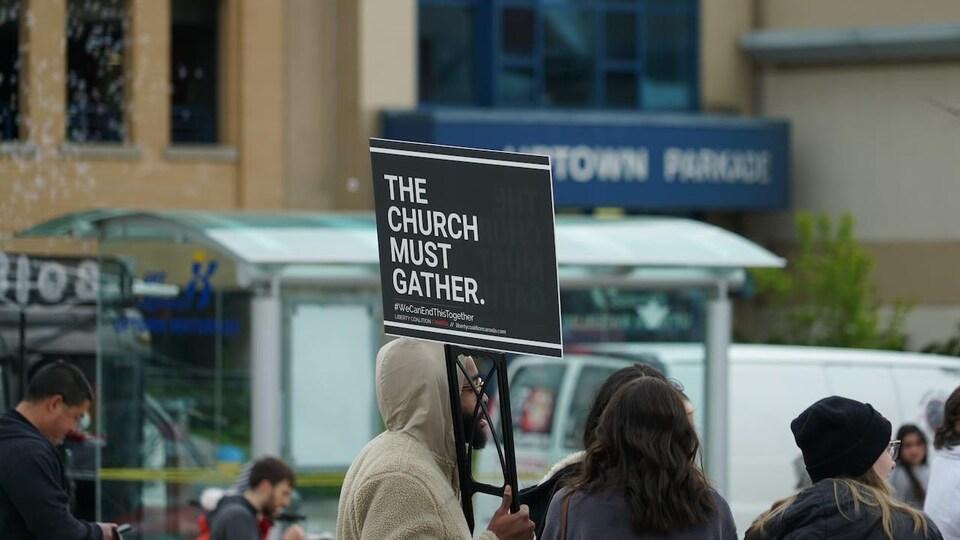 Une personne tient une pancarte.