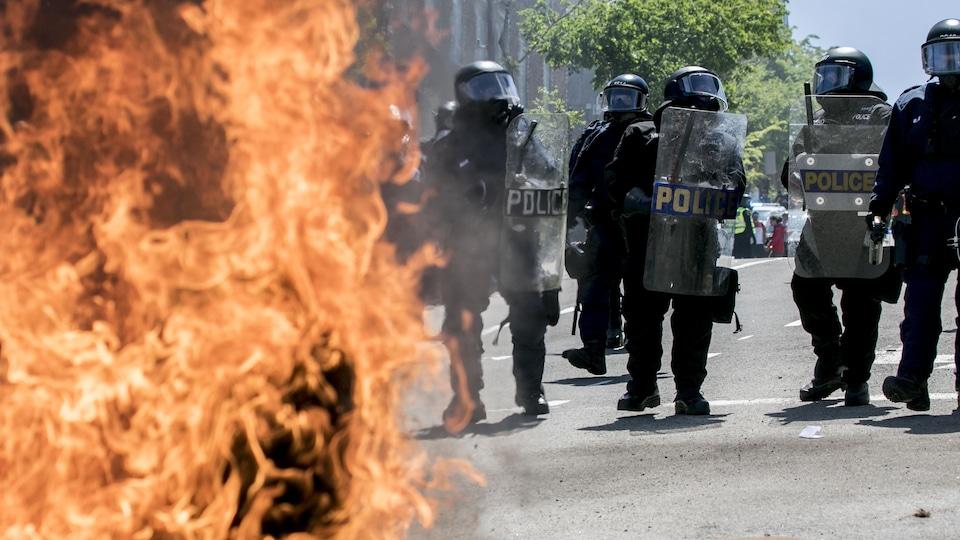 Des policiers de l'escouade antiémeute forment une ligne. À l'avant-plan, on aperçoit un meuble en train d'être consumé par les flammes.