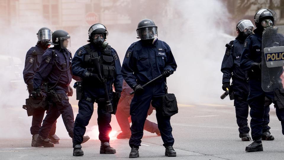 Des policiers font face à la foule.