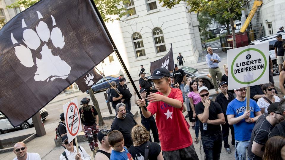 Un enfant agite un drapeau de La Meute sous la supervision de ses parents.