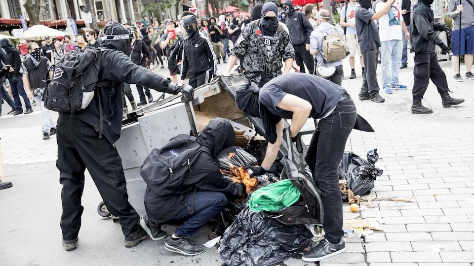 Des manifestants masqués vident un conteneur à déchets lors de manifestations à Québec