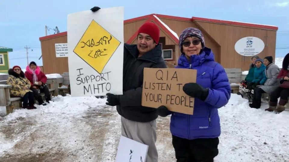 Deux manifestants tiennent des pancartes.