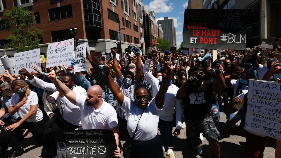 Une foule de manifestants, un genou par terre et les bras levés au ciel, sont arrêtés dans une rue du centre-ville pendant leur marche.