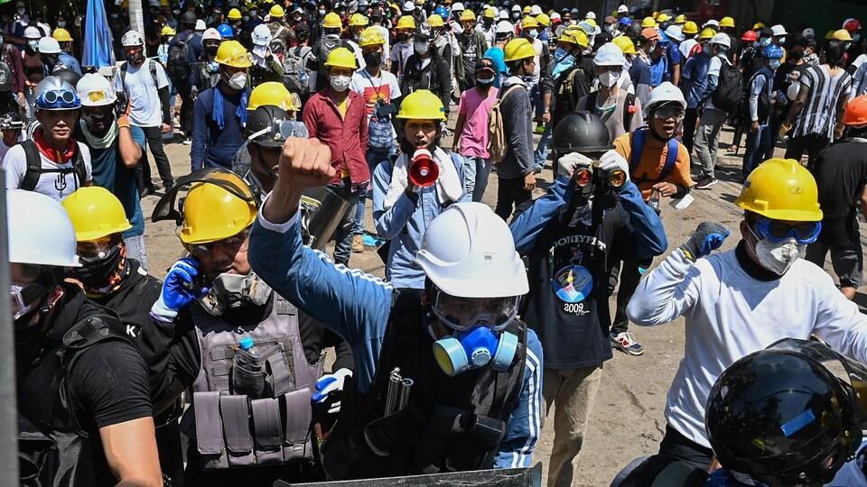 Des centaines de manifestants avec des masques et des casques.