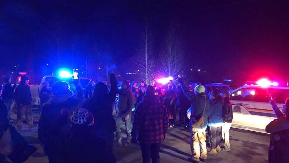 Des manifestants sont rassemblés près de véhicules de la police.