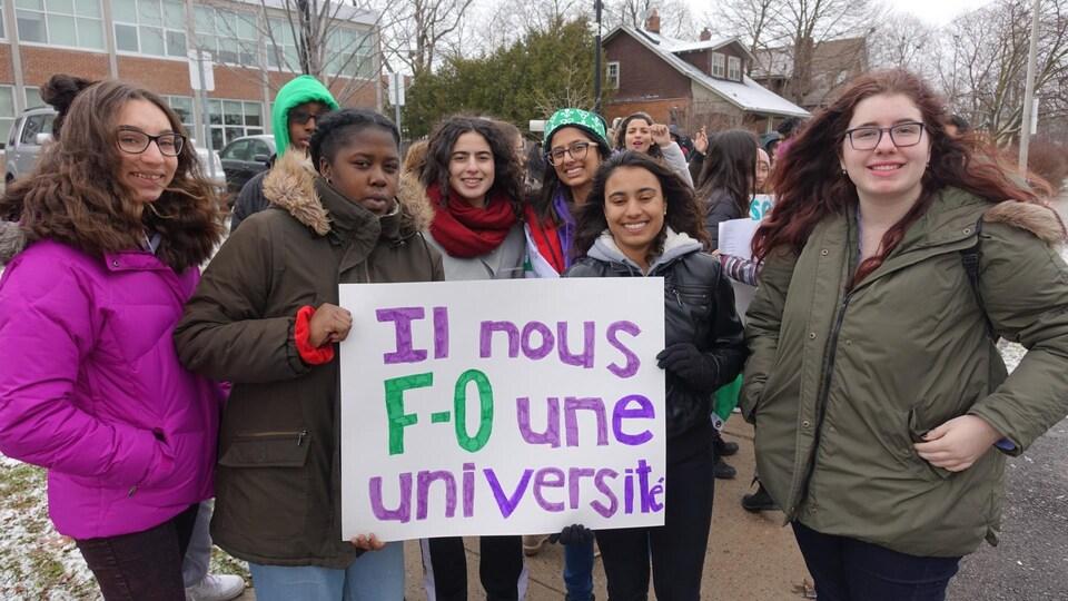 Photo d'élèves à l'extérieur tenant une affiche disant «Il nous F-O une université».