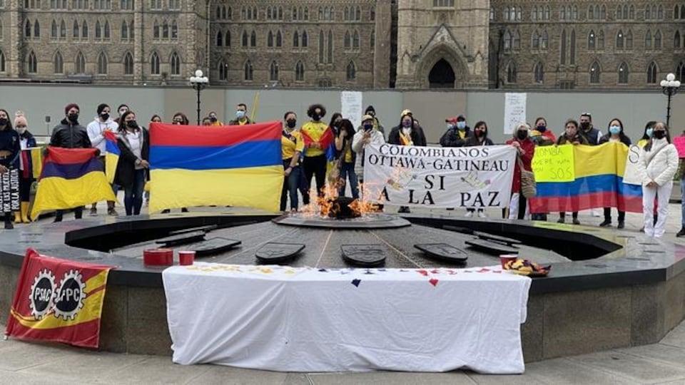Des manifestants portants le masque brandissent le drapeau de la Colombie devant la flamme du centenaire.