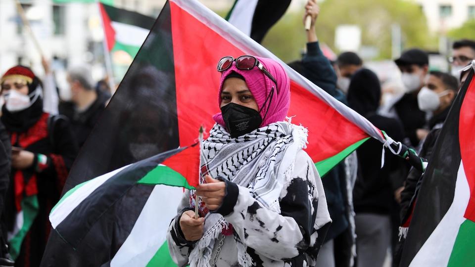 Une femme tient un drapeau palestinien.