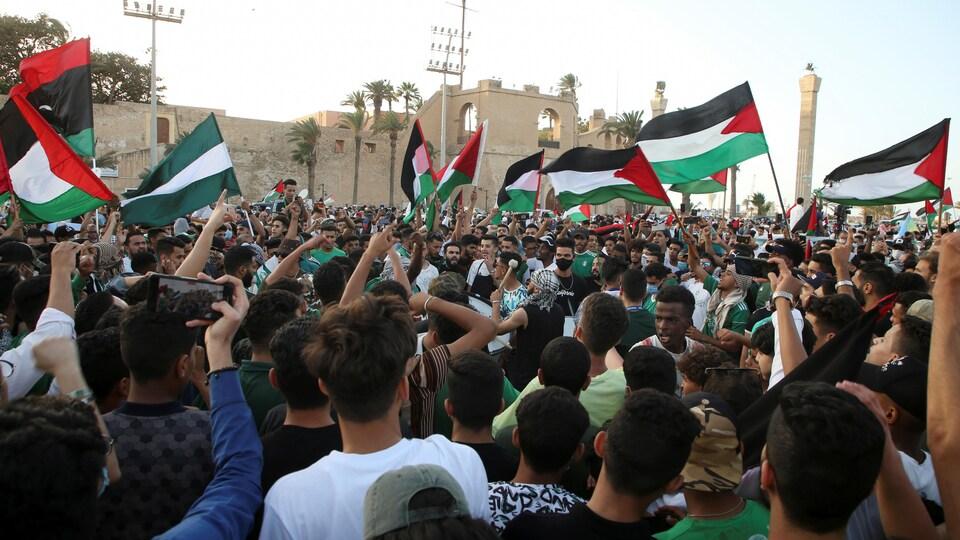Des gens sont massés devant une mosquée et brandissent des drapeaux palestiniens.