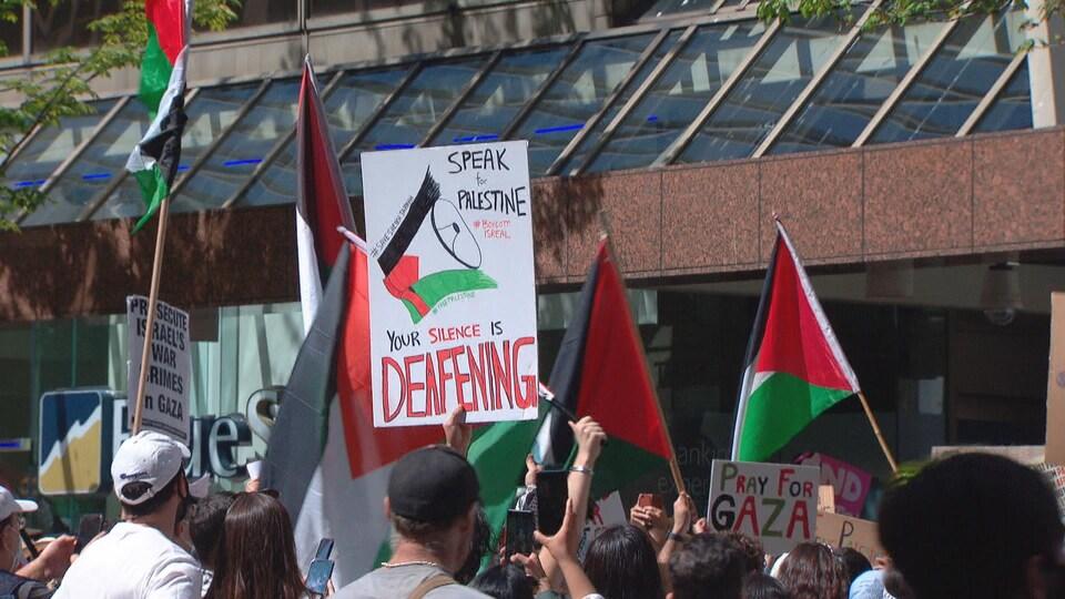 Des manifestants brandissent des pancartes et des drapeaux palestiniens devant un immeuble.