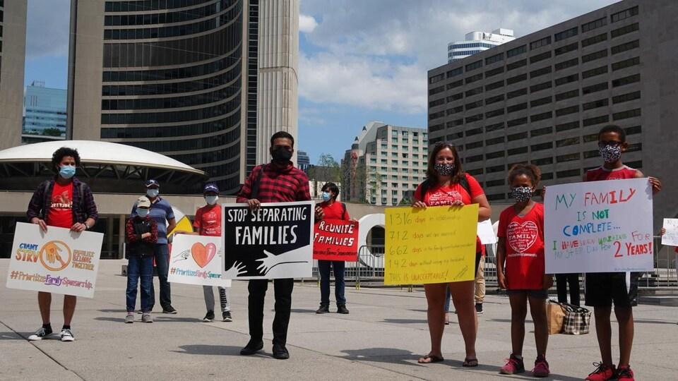 Des manifestants avec des pancartes devant l'hôtel de ville de Toronto.