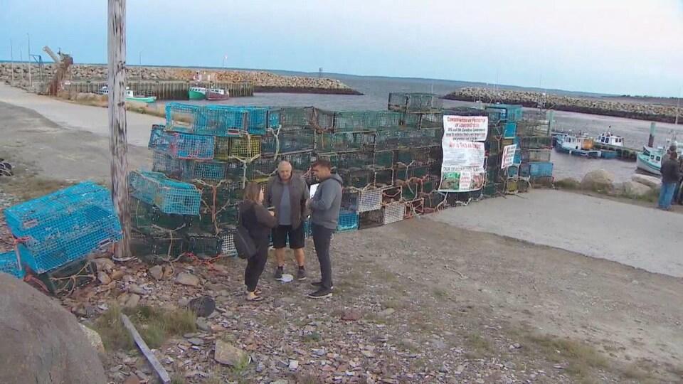 Trois personnes groupées devant une barricade faite de casiers à homard.