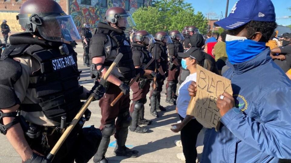 Un jeune homme noir, portant un masque et une casquette, tient une pancarte face à un policier antiémeute.