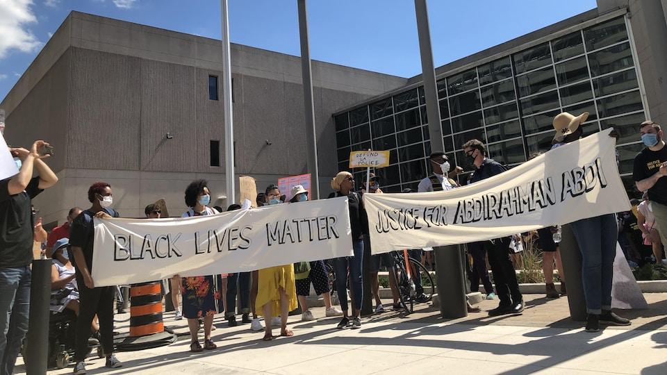 Des personnes tiennent des bannières sur lesquelles il est écrit «La vie des Noirs compte» et «Justice pour Abdirahman Abdi».