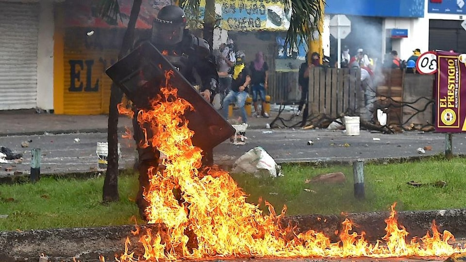 Un officier se protège des flammes avec son bouclier.