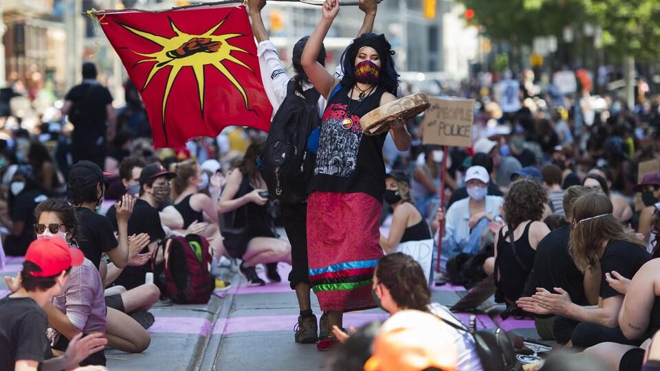 Une femme avec un drapeau et un tambour au milieu de manifestants.