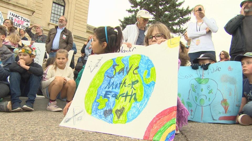 Certains tiennent des pancartes avec des dessins de la Terre et des slogans en anglais. « Sauvons la Terre, notre mère » ou « sauvons le futur ».