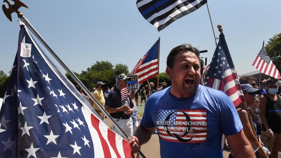 Un homme brandissant un drapeau américain porte un tee-shirt à l'effigie de QAnon.
