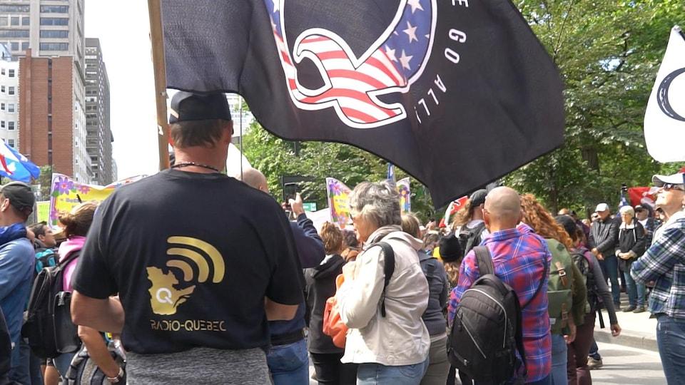 Des gens lors d'une manifestation. Certains agitent des drapeaux du mouvement QAnon.