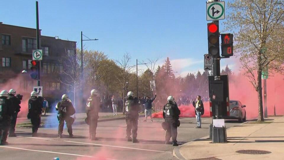 Des policiers casqué sont placés en ligne face à des manifestants qui ont lancé des fumigènes.