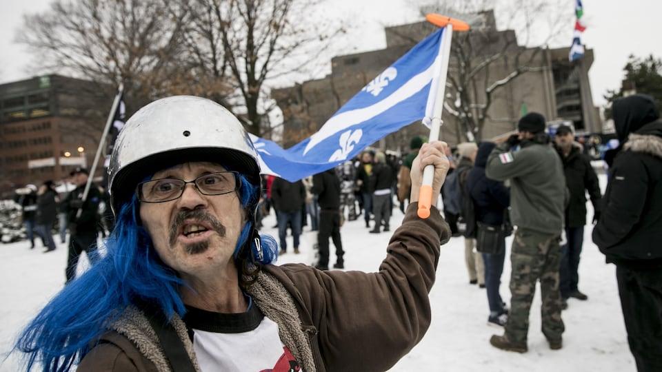 Un homme casqué brandit un drapeau du Québec lors d'une manifestation dans la capitale.