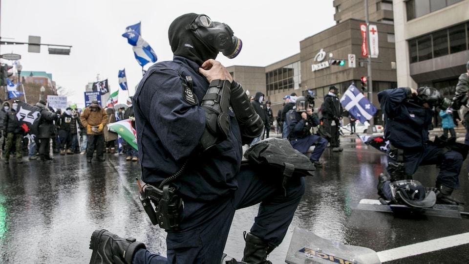 Des policiers enfilent des masques à gaz devant des manifestants.