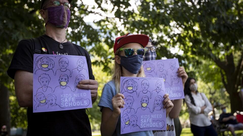 Un enfant et un adulte sont dans un parc. Ils sont masqués et ont dans les mains une affiche.