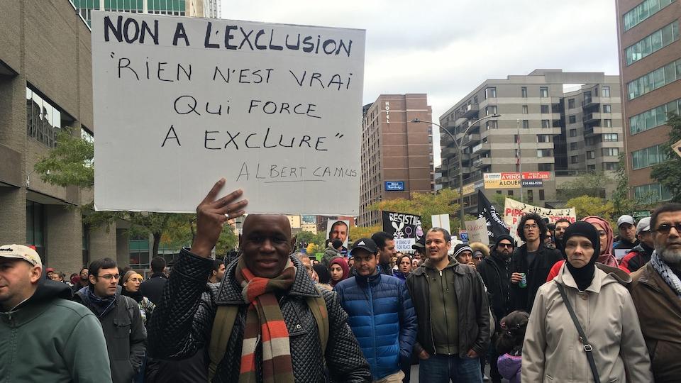 Des manifestants dont l'un tient une pancarte sur laquelle on peut lire «Non à l'exclusion. Rien n'est vrai qui force à exclure. Albert Camus».