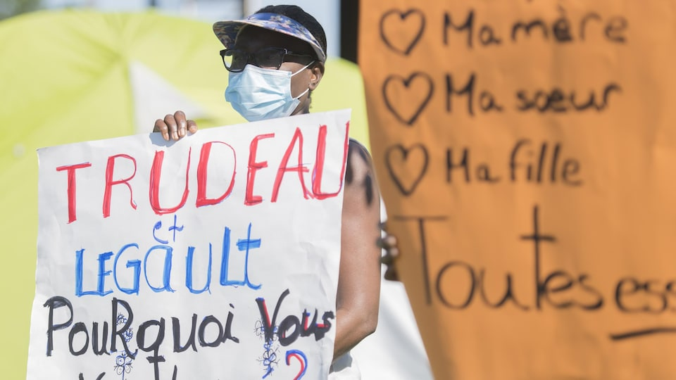 Des gens manifestent avec un panneau visant Justin Trudeau et François Legault.