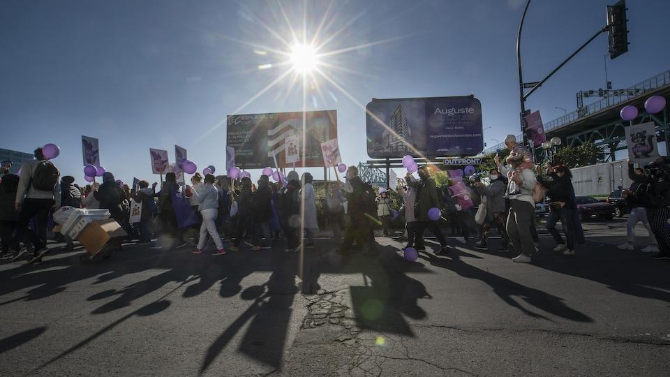 Des manifestants avec des ballons marchent dans une rue.