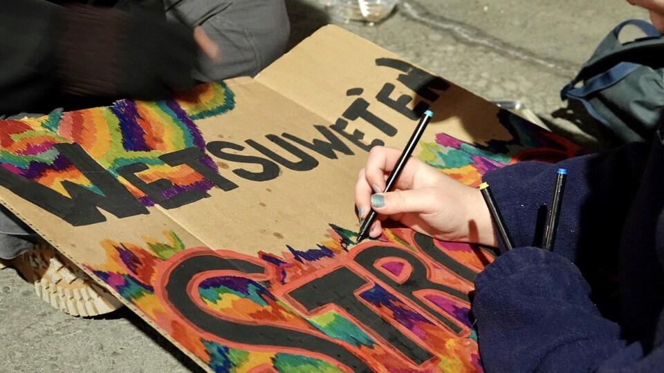Une manifestante colorie une affiche sur laquelle on peut lire « Wet'suwet'en Strong ».