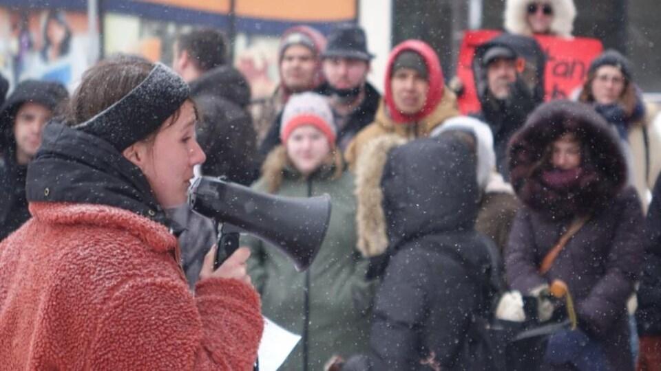 Une femme avec un megaphone devant des manifestants