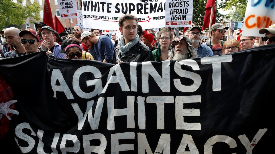 Des personnes, qui tiennent des pancartes, marchent derrière une banderole noire disant « Contre la suprématie blanche » en anglais.