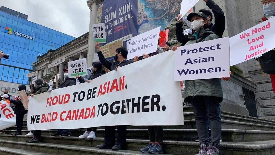 Des manifestants tiennent des affiches avec des slogans contre le racisme anti-asiatique.