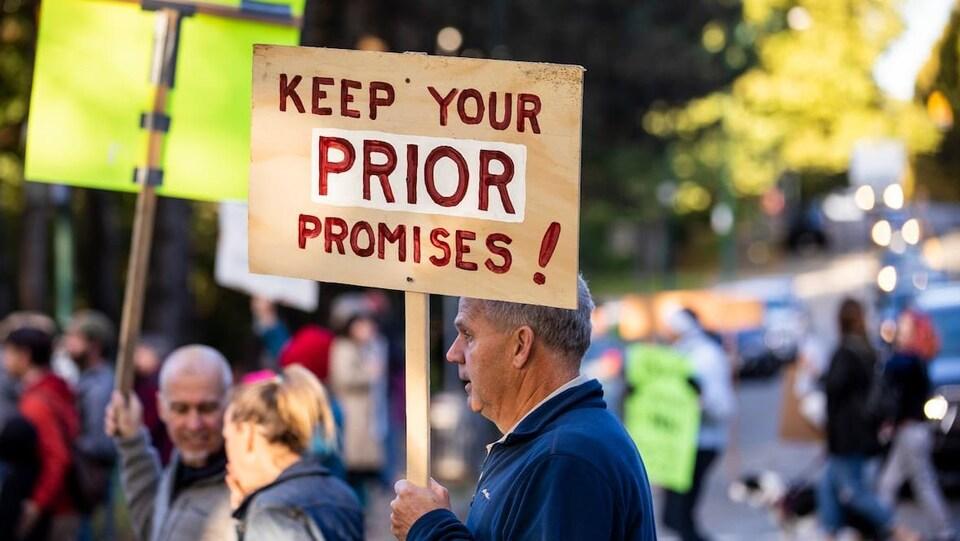 Des manifestants dans une rue de Vancouver, l'un d'eux porte une affiche qui indique : «Tenez vos promesses au sujet de Prior!»