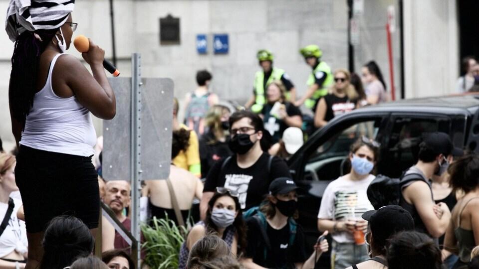 Une femme parlant au micro devant des manifestants.