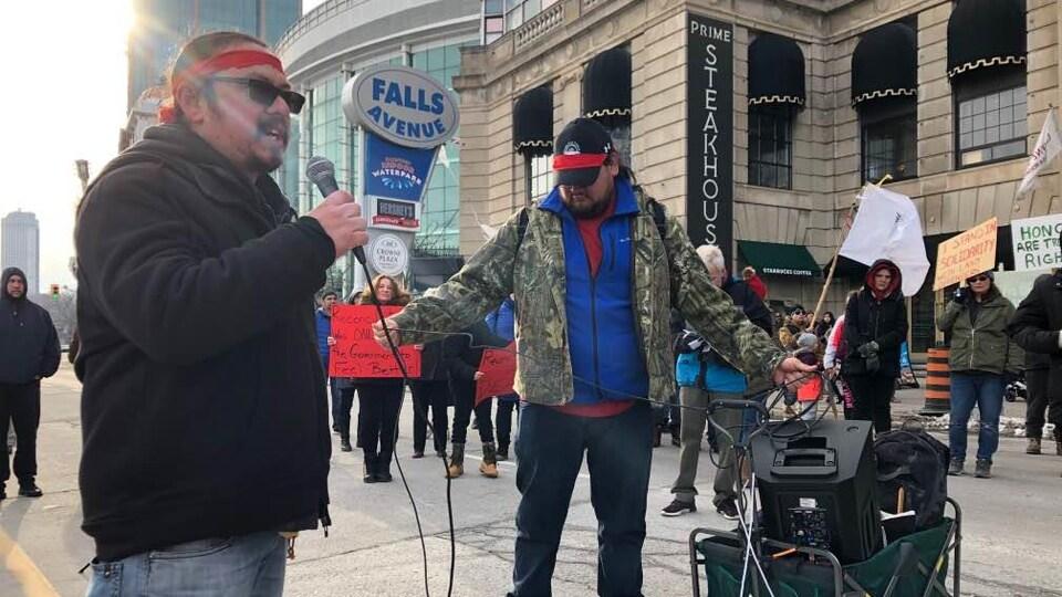 Des hommes avec un système de sonorisation au milieu d'une foule tenant des pancartes.